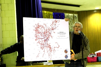 A speaker holds up a map of bus routes eliminated under the second scenario