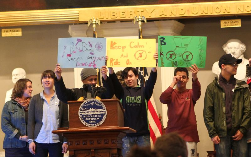 Students from Bikes Not Bombs hold up pro-bicycling signs.