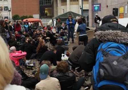 A large group of people listen and respond to a speaker at Occupy Boston
